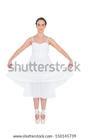 Peaceful young ballet dancer standing on her tiptoes on white background  - stock photo