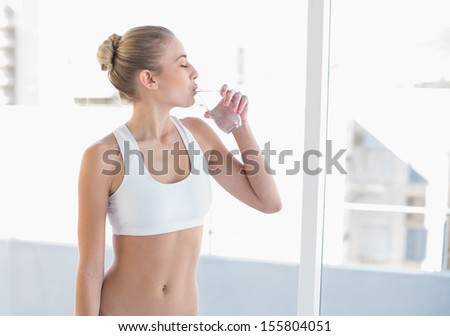 Peaceful young blonde model in white sportswear drinking water