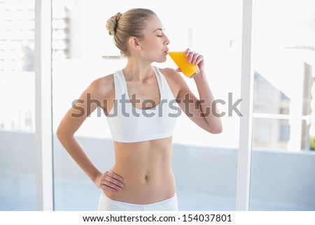Peaceful young blonde model in white sportswear enjoying orange juice - stock photo