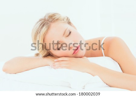 Peaceful young blonde sleeping on her bed at home in the bedroom - stock photo