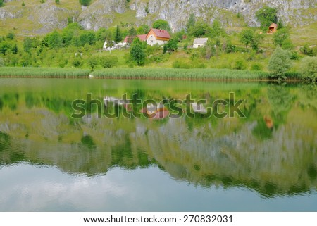 peacefull farm landscape reflected in Komarnica River, Montenegro - stock photo