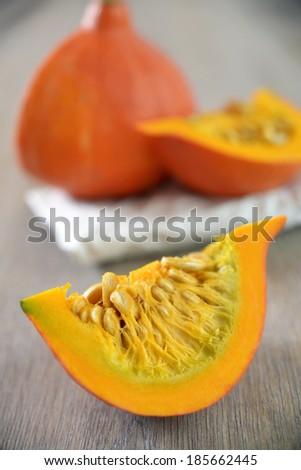 peaces of a hokkaido pumpkin on wooden background - stock photo
