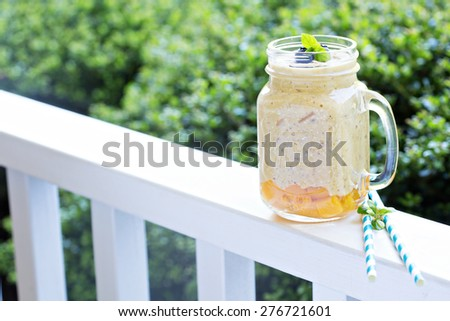Peach and mango smoothie with oats healthy breakfast outdoor in the morning - stock photo