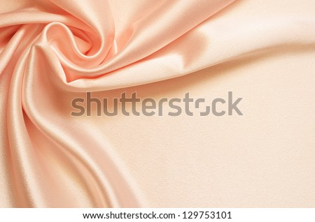 Peach background with satin drapery in the corner - stock photo