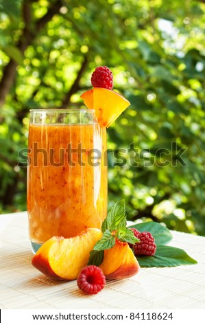 Peach cocktail in the garden in hot summer, sunny day with raspberries - stock photo