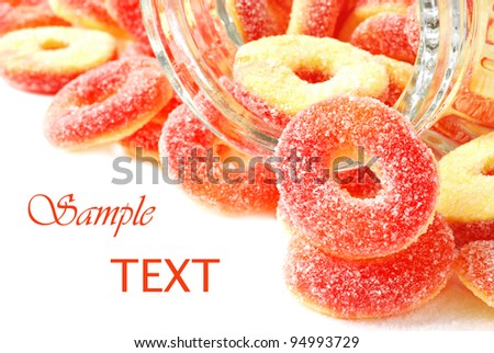 Peach flavored candy rings spilling from glass jar on white background with copy space.  Macro with shallow dof. - stock photo