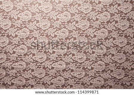 Peach lace sits on a brown background. - stock photo