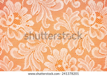 Peach lace sits on a oreng background - stock photo