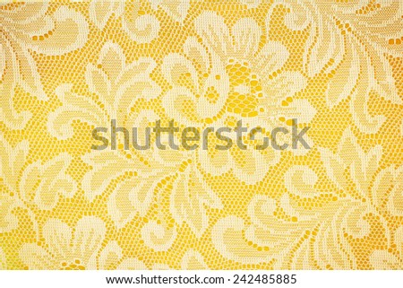 Peach lace sits on a yellow background - stock photo