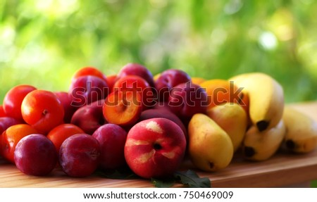 peach, pear, plums and bananas on table