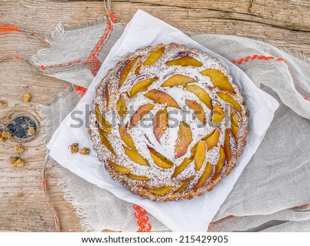 Peach pie with sugar powder over a piece of paper and a linen table cloth on a rough old wooden surface - stock photo