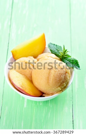 Peach sorbet with fruit slices and mint in bowl - stock photo