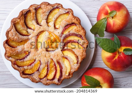 peach tart and fresh fruit closeup on wooden background horizontal view from above   - stock photo
