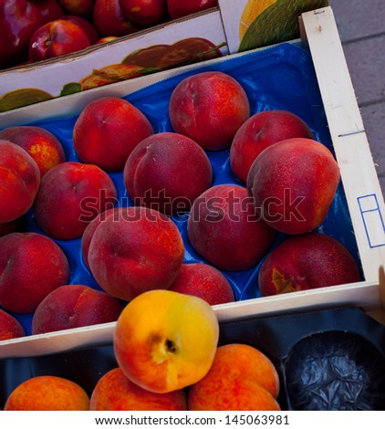 peaches and apricots in the boxes, tropical fruit - stock photo