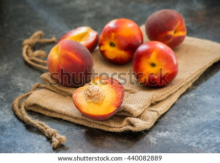Peaches and nectarines on rustic napkin over dark background, selective focus, closeup