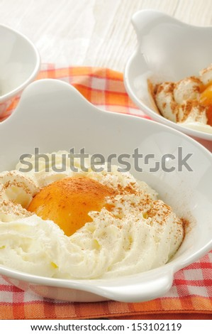 peaches in syrup and whipped cream as dessert - stock photo