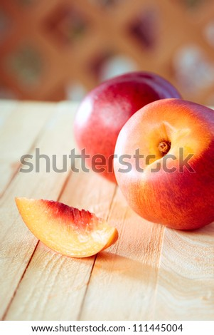 peaches with a slice of a peach on a wooden table