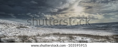 Peak District moorland panorama. A weak mid winter sun shines down on the wintry moorland that forms the boundary between Cheshire, Staffordshire and Derbyshire. - stock photo