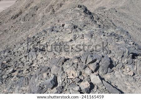 Peak of rocky mountain in arid desert landscape  - stock photo
