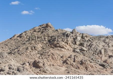 Peak of rocky mountain in arid desert landscape against blue sky background - stock photo