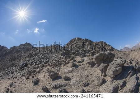 Peak of rocky mountain in arid desert landscape against blue sky background with sun - stock photo