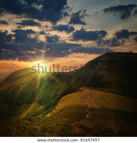 peak of the hill with pathway and mountain sunset rays on cloudy sky - stock photo