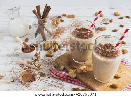 Peanut and almond butter banana oat smoothie with paper straws on a wooden rustic table - stock photo