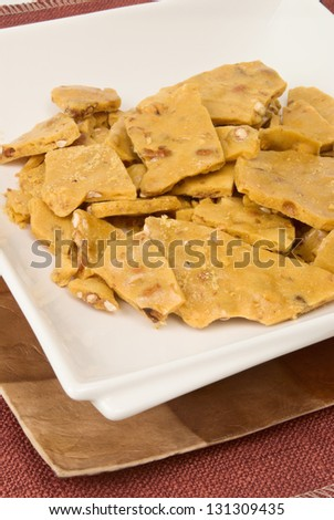 peanut brittle candy all broken up in little pieces for easier eating. Served on double plates. - stock photo
