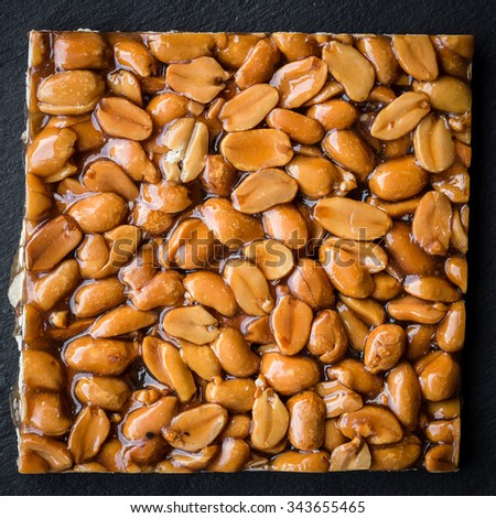 Peanut brittle on black background - stock photo