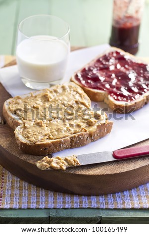 peanut butter and jelly sandwich with glass of milk, close up. - stock photo