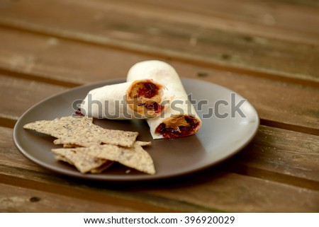 peanut butter and jelly wrap with chips on a plate - stock photo
