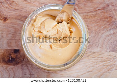 peanut butter and knife in a glass jar on wooden table