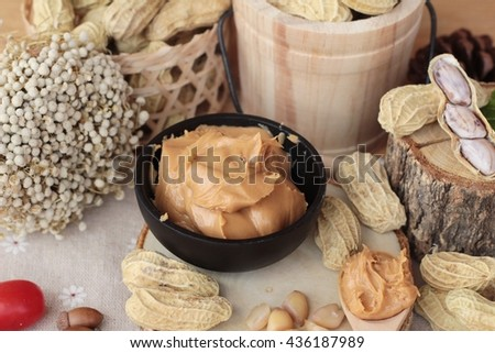 Peanut butter and peanut on wood background - stock photo