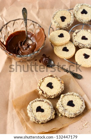 Peanut butter cookies with heart print coated with chocolate and nuts - stock photo