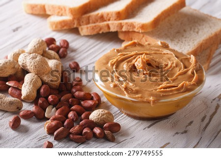 peanut butter in a bowl close-up on a table and toast. horizontal  - stock photo