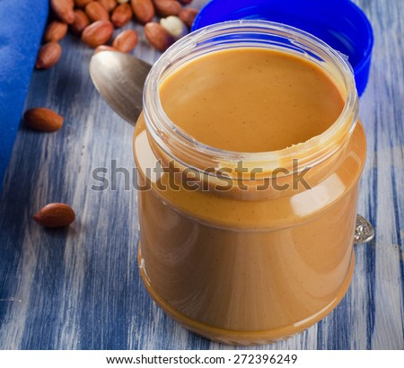 Peanut butter in a jar on blue background.  Shallow dof. - stock photo