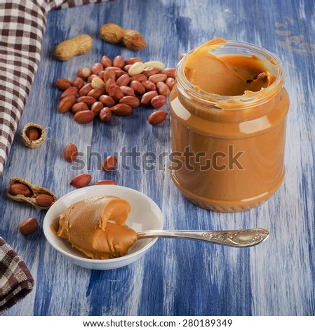 Peanut butter in a spoon  with peanuts.  Shallow dof. - stock photo