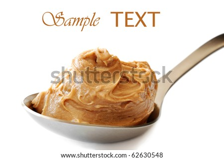 Peanut butter in large serving spoon on white background with copy space.  Macro with shallow dof. - stock photo