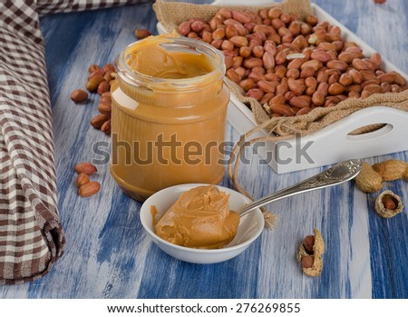 Peanut butter in  spoon and box of peanuts.  Shallow dof. - stock photo