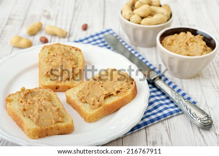Peanut butter sandwich on plate with nuts on wooden background