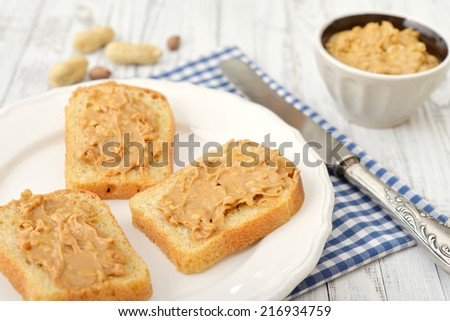 Peanut butter sandwich on plate with nuts on wooden background - stock photo