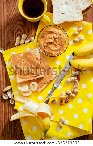 peanut butter sandwich with black tea, bananas and peanuts on the wooden background