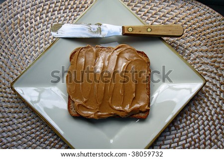 Peanut butter spread on bread with spatula on white plate.