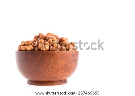 Peanut in wooden bowl isolated on white background - stock photo