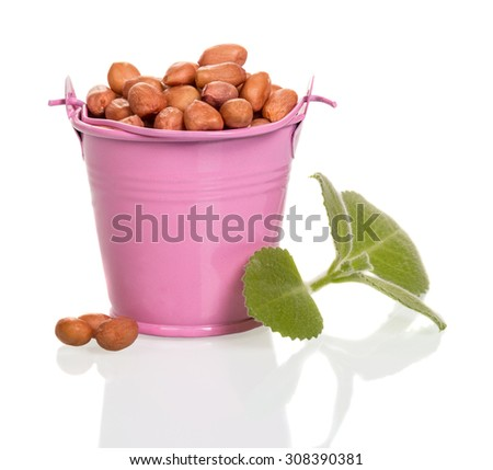 Peanuts in a pink bucket on a white background - stock photo