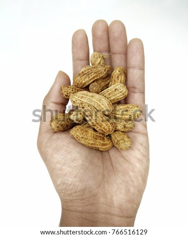 Peanuts in hand isolated on white background.