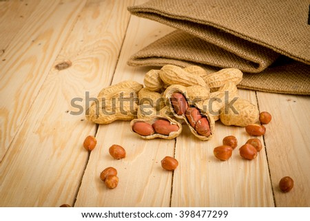 Peanuts on a wooden background .