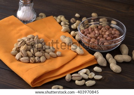 Peanuts, pistachios, various nuts. On a bright orange table cloth With white salt. Very good snacks with beer or booze. Traditional European fare. - stock photo