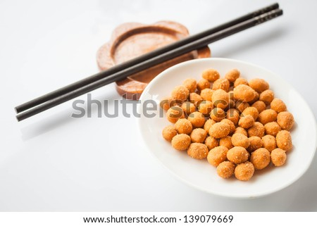 Peanuts snack coated with spicy seasoning and chopsticks - stock photo