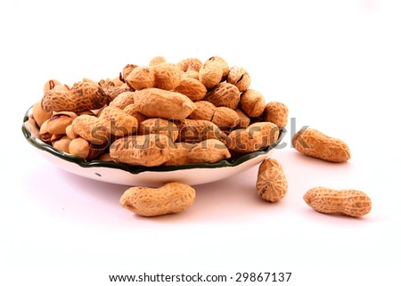 peanuts with shells on the plate isolated on white